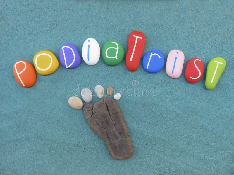 Podiatrist, медицинское профессиональное слово составленное с multi покрашенными камнями над влажным песком стоковое фото