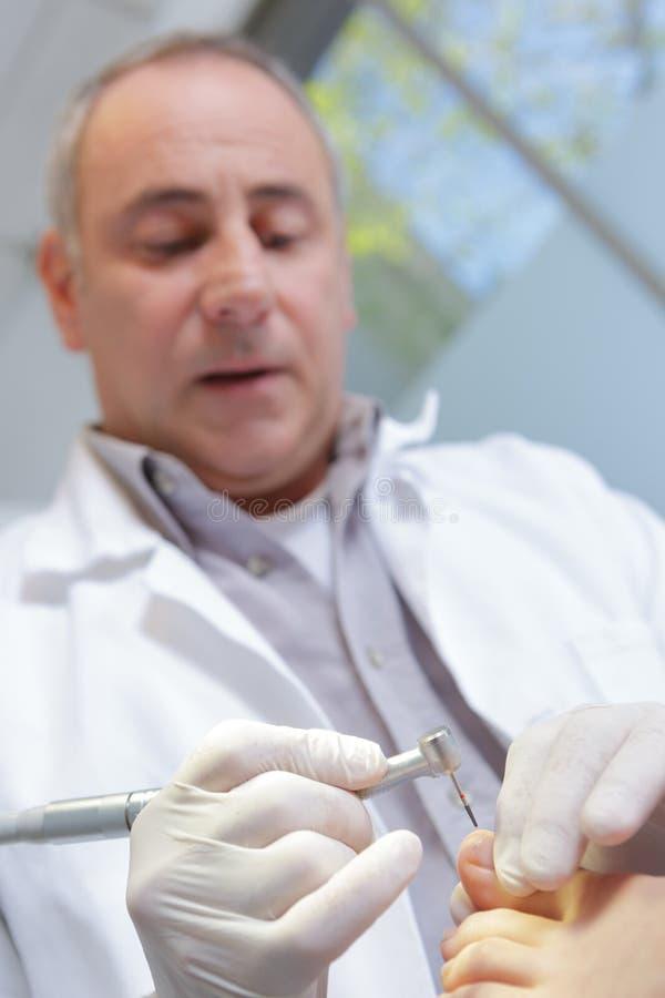 Podiatrist pomaga pacjenta z chiropody zdjęcie stock