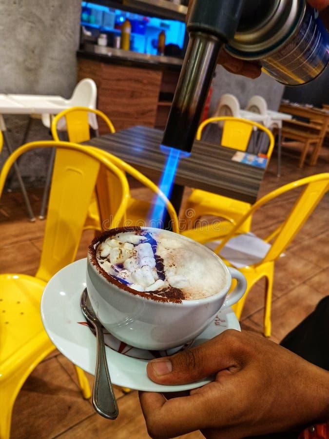 Podkładać ogień w marshmallow w filiżance gorąca czekolada i sztuka jedzenie Podkładać ogień w marshmallow w filiżance gorąca cze fotografia stock