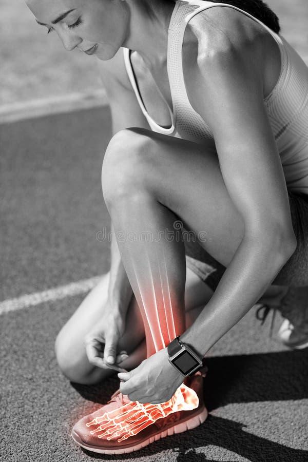 Podkreślać kości wiąże obuwianą koronkę na biegowym śladzie kobieta zdjęcia stock
