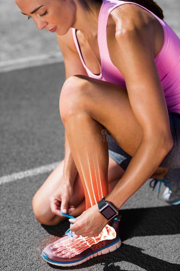 Podkreślać kości wiąże obuwianą koronkę na biegowym śladzie kobieta fotografia royalty free