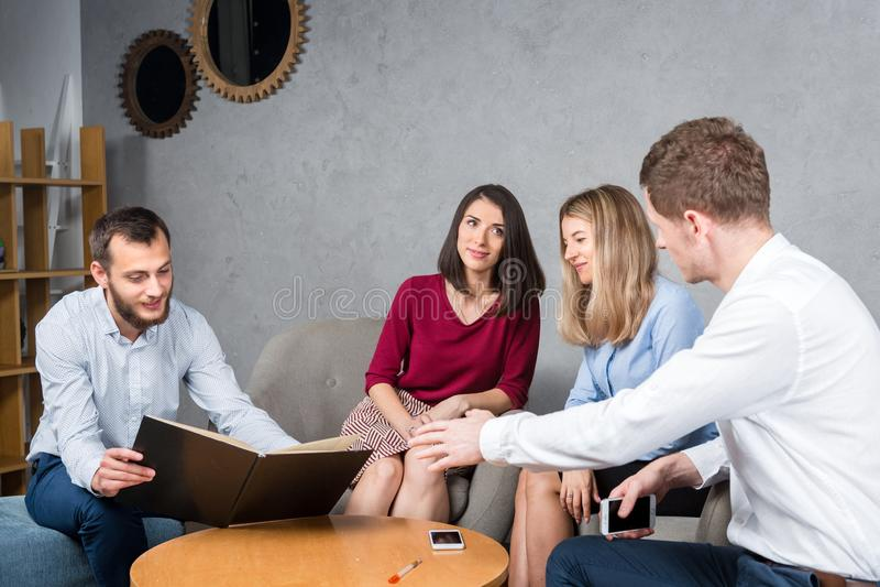Podległa biznesowa sytuacja, praca zespołowa Grupa młody Kaukaski cztery ludzie siedzi w biurze przy round stołem obraz royalty free