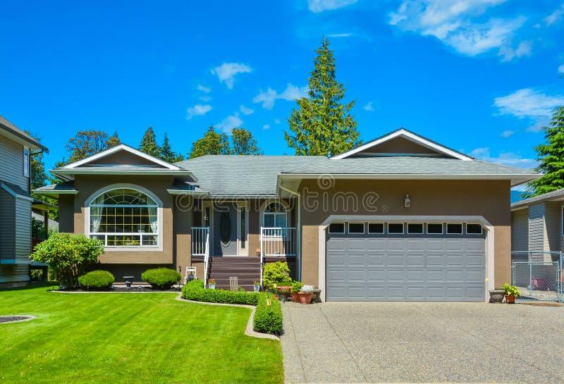 Podmiejski rodzina dom z ładnym gazonem, szerokim garażu drzwi i betonowym podjazdem, fotografia stock