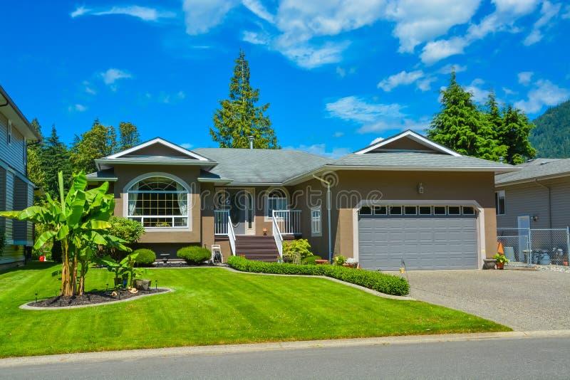 Podmiejski rodzina dom z ładnym gazonem, szerokim garażu drzwi i betonowym podjazdem, obrazy royalty free