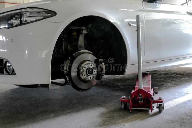 Podnoszenie samochodu w celu wymiany opon na parkingu , zużyte podwozie do wymiany opony zdjęcie royalty free