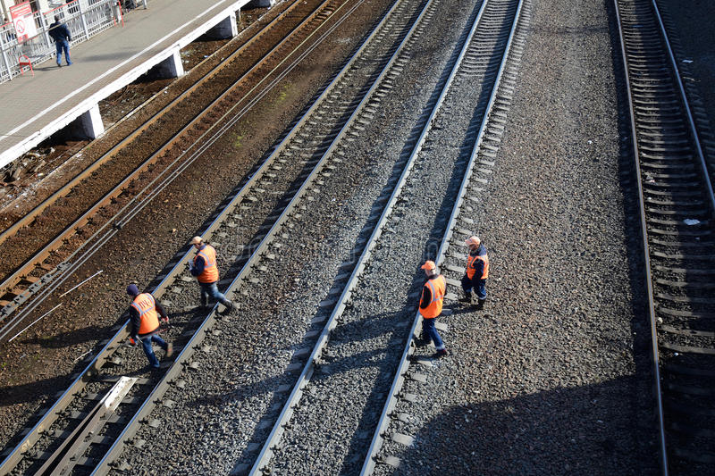 PODOLSK, RUSSIAN FEDERATION - APRIL, 13, 20015: railway workers. Crossing the rails in sunny weather stock photo