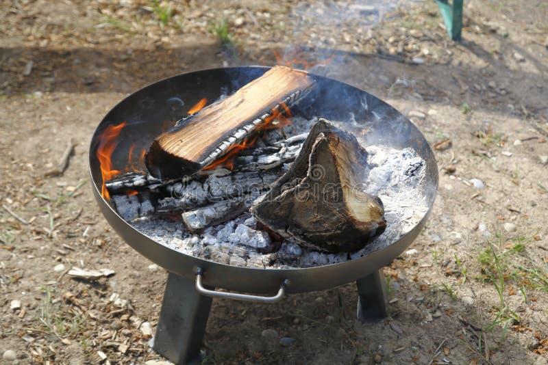 Podpala w pożarniczym pucharze, duży drewniany grill z żużlem fotografia royalty free