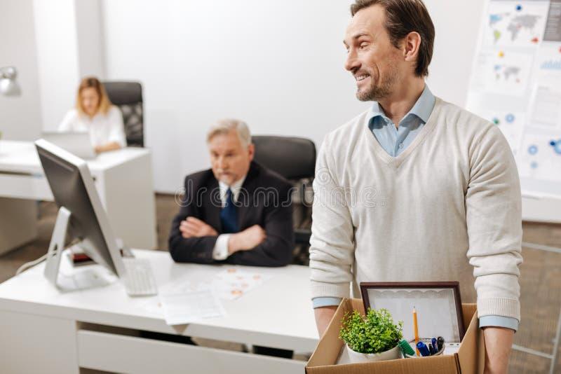 Podpalający uśmiechnięty pracownik niesie pudełko i rezygnuje pracę zdjęcie royalty free