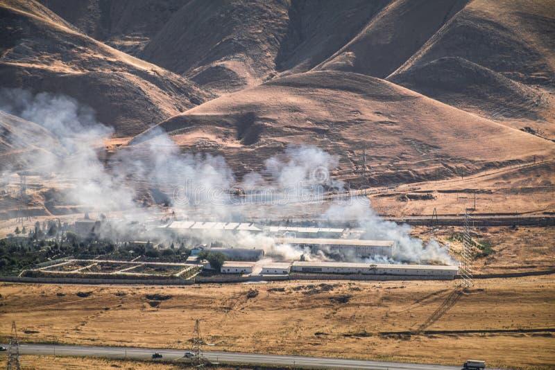 Podpalenie przemysłowy magazyn, duży dymnej chmury podesłanie z wiatrem Masywna szkoda na firma budynku ogarniających w akademiac obraz royalty free