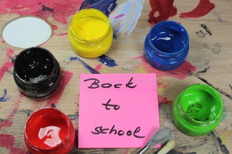 Podpisuje szkoły ` na farba barłogu z farb narzędziami, Z powrotem obraz stock