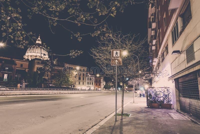 Podpisuje w kierunku bazyliki Di San Pietro i kopuła przy nocą w watykanie zdjęcie stock