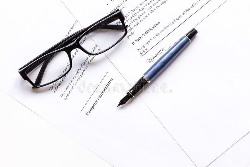 Podpisywać kontrakt z piórem i szkła w biznesowej pracy odgórnym widoku obrazy stock