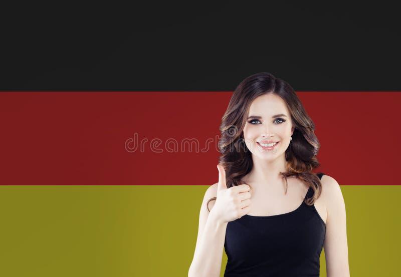 Podróż w Niemcy pojęciu Ładna kobieta pokazuje kciuk w górę Greckiego chorągwianego tła przeciw zdjęcie royalty free