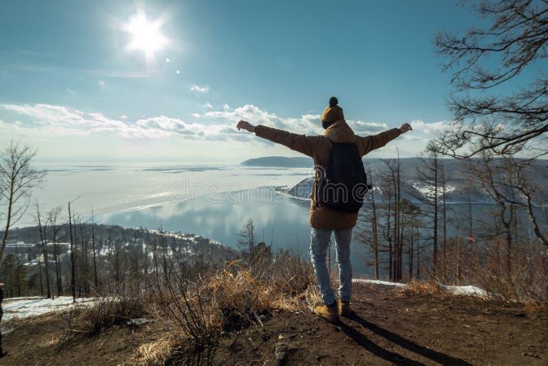Podróżników stojaki na górze i spojrzenia przy pięknym widokiem jeziorny Baikal Styczeń 33c krajobrazu Rosji zima ural temperatur zdjęcie stock