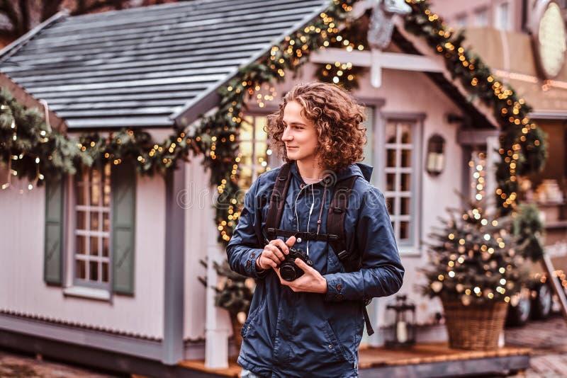 Podróżnika młodzi przystojni kędzierzawi uśmiechy, spacery przez wakacyjnego miasta fotografia stock