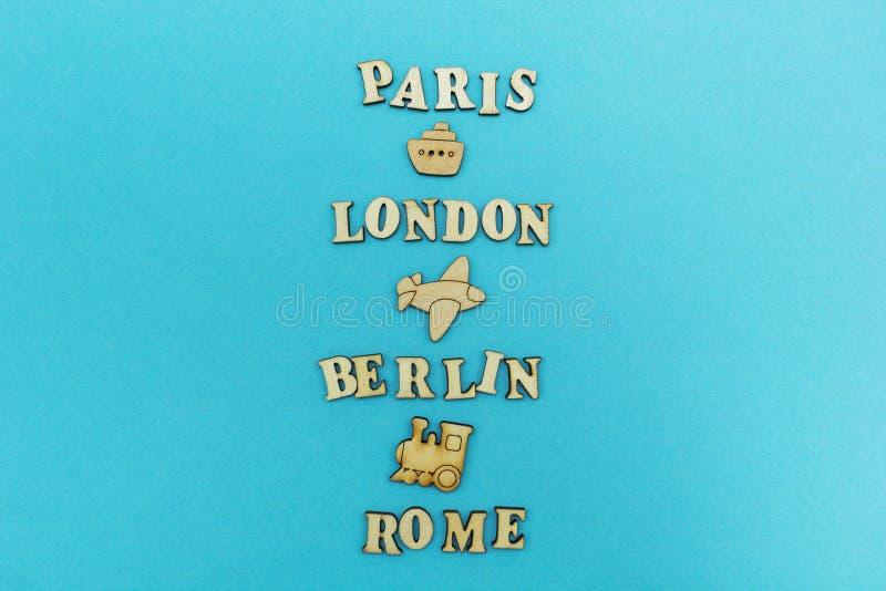 Podróż dookoła świata imiona miasta: «Paryż, Londyn, Berlin, Rzym «na błękitnym tle Drewniane postacie samolot, zdjęcie royalty free