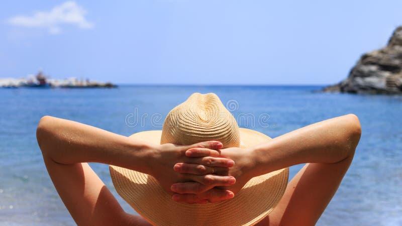 Podróż, powołanie, wakacyjny pojęcie Kobieta w kapeluszu kłama na deckchair na plaży morzem zdjęcie royalty free