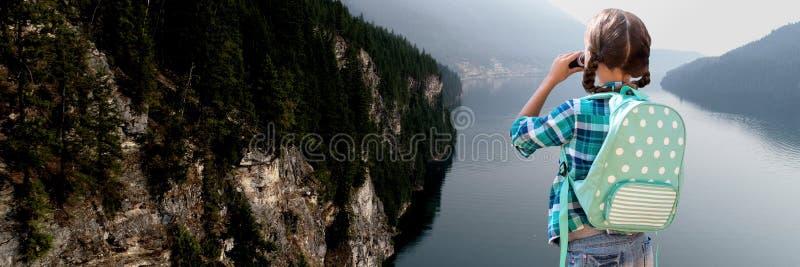 Podróżna dziewczyna z torbą i lornetkami przed krajobrazem zdjęcie royalty free