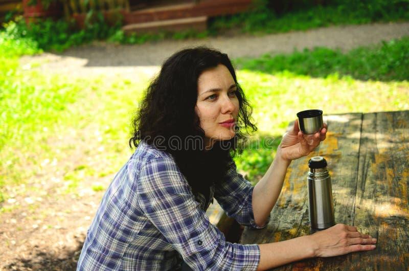 Podróżni kobieta napoje od termos butelki nakrętki obrazy stock
