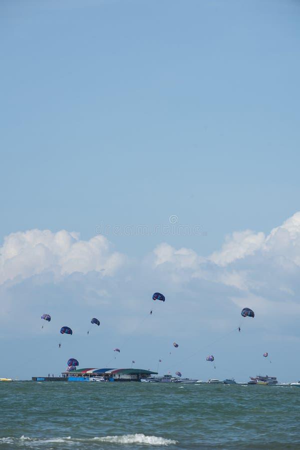 Podróżnicy bawić się kolorowego parasailing przy Pattaya, Tajlandia zdjęcia stock