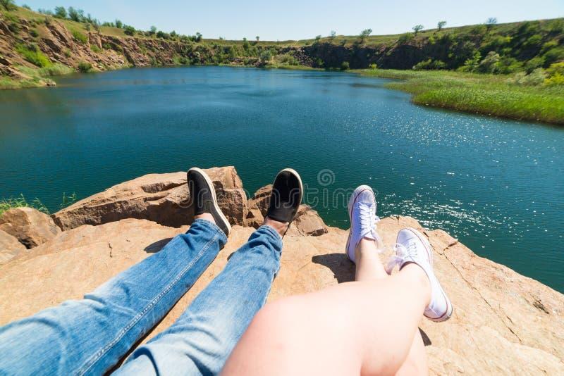 Podróżnicy dobierają się w sportów butach na górze blisko rzeki w tle natura Mężczyzna i kobieta Para siedzi th i robi obrazy royalty free