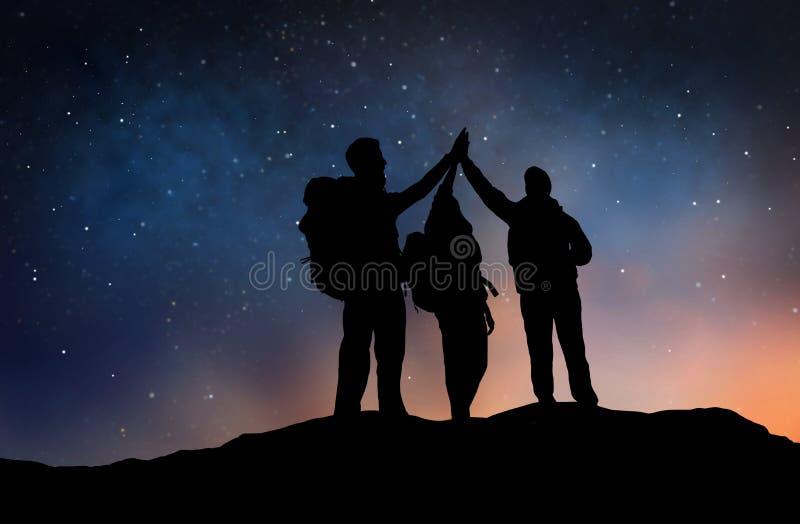 Podróżnicy robi wysokości pięć nad gwiaździstym nocnym niebem fotografia stock