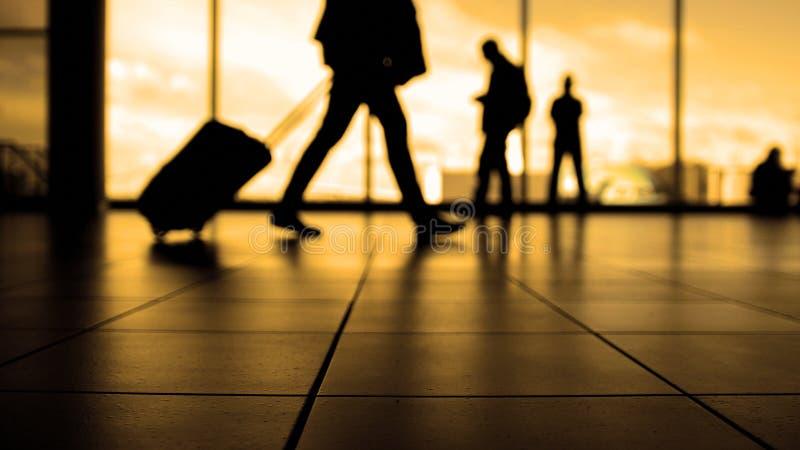 Podróżnicy w lotniskowym odprowadzeniu odjazdy eskalatorem przed okno, sylwetka, ciepła zdjęcie stock