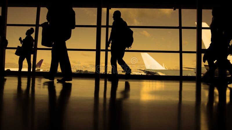 Podróżnicy z walizkami i bagaż w lotniskowym odprowadzeniu odjazdy przed okno, sylwetka, ciepła obrazy stock