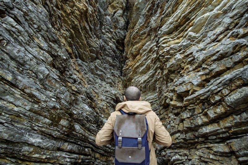 Podróżniczy modnisia mężczyzna z plecakiem cieszy się widok skały zdjęcie royalty free