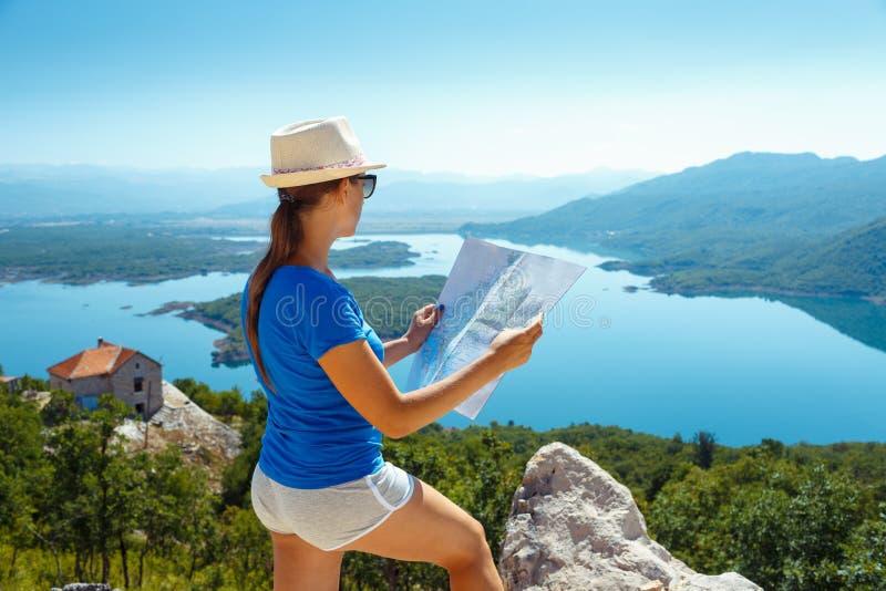 Podróżnik dziewczyny gmerania właściwa wskazówka na mapie, wolności i akcie, obraz royalty free