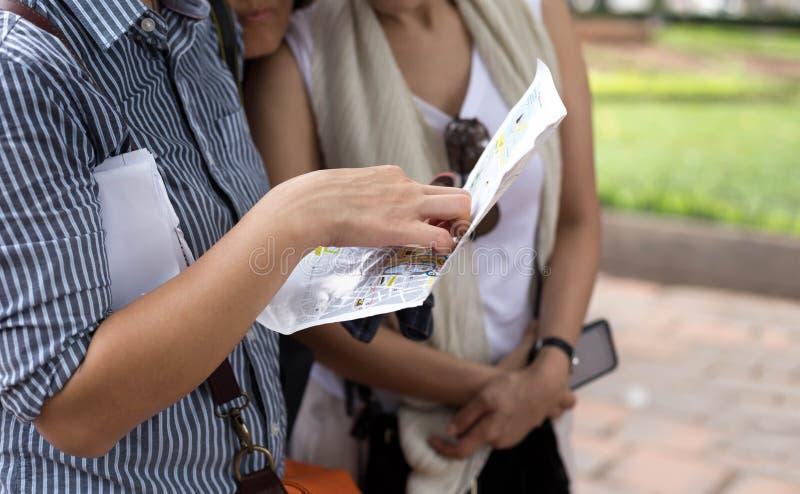 Podróżnik grupa kobiety gmerania właściwa wskazówka na miasto mapie zdjęcie royalty free