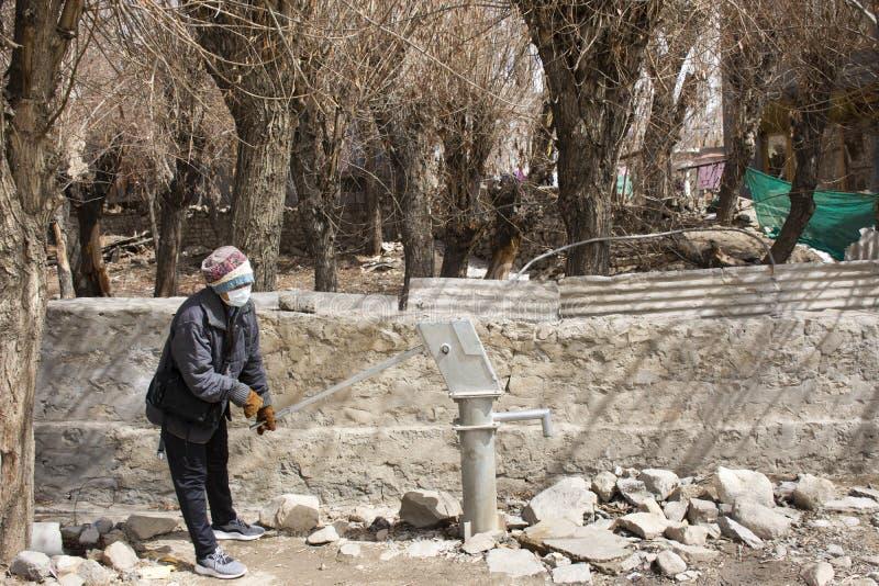 Podróżnik kobiet tajlandzki test używa antykwarską wody gruntowe manuału dźwigni pompę dobrze przy plenerowym w alei Ladakh wiosk fotografia stock