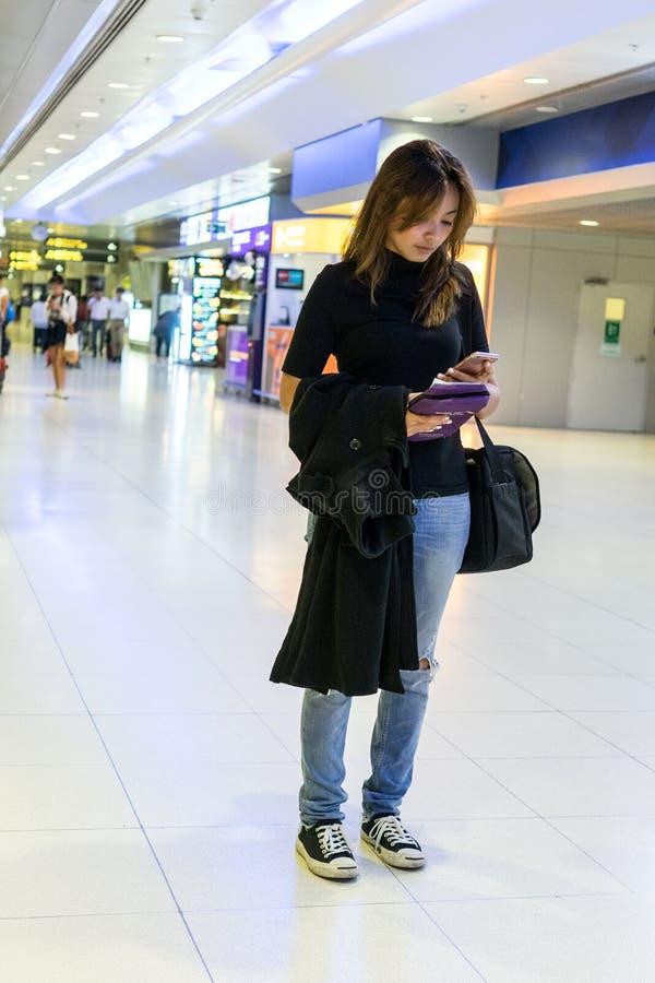 Podróżnik kobiety Żeńscy podróżnicy trzyma mobilnymi czeków loty przy lotniskiem fotografia royalty free