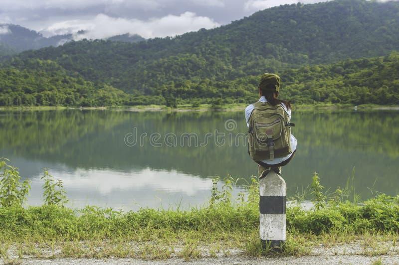 Podróżnik kobiety obsiadanie z plecakiem cieszy się zmierzch na szczytu mou obrazy royalty free