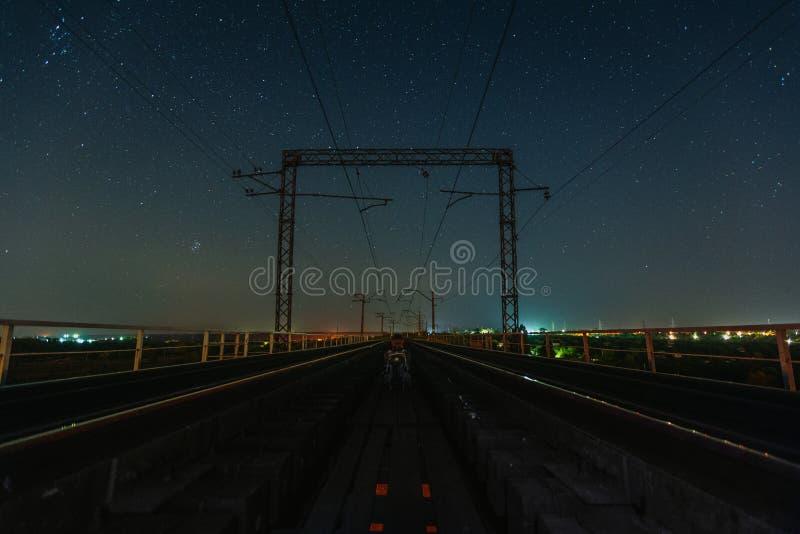 Podróżnik siedzący między dwiema kolejami pod gwiazdami obraz stock