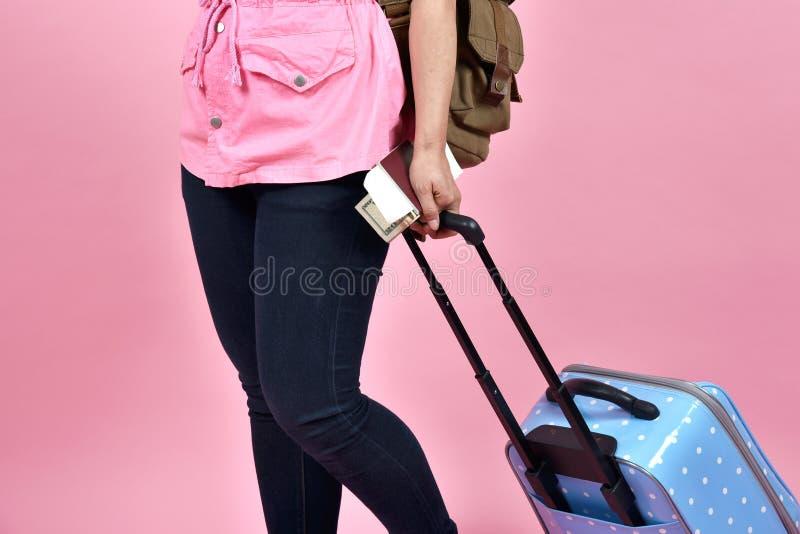 Podróżnik trzyma błękitną walizkę i paszportowego dokument nad różowym tłem obrazy royalty free