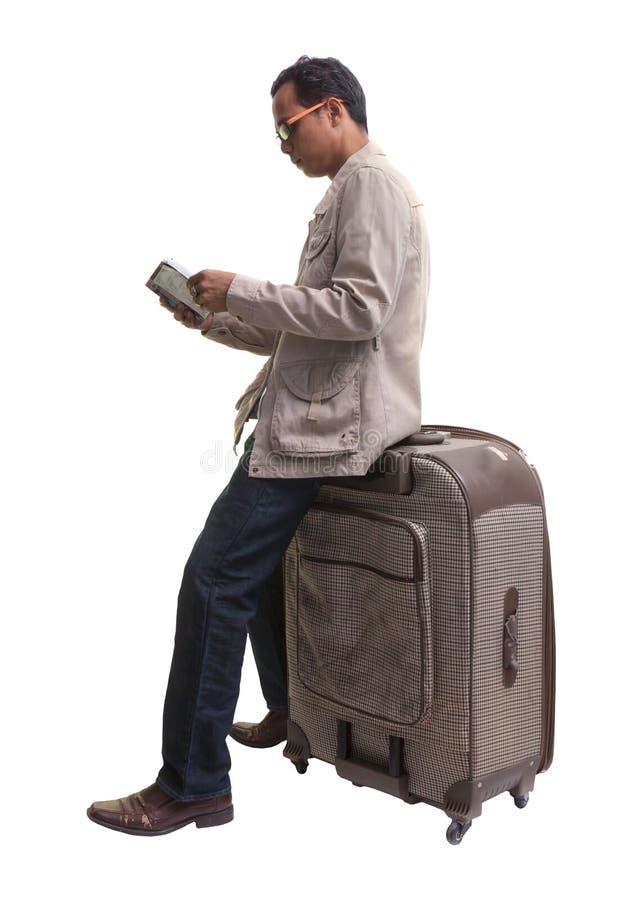 Podróżnik trzyma czytanie i książkę podczas gdy siedzący na dużej walizce obraz royalty free
