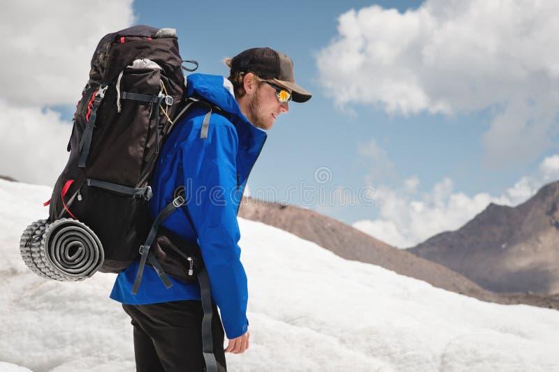 Podróżnik w nakrętce i okularach przeciwsłonecznych z plecakiem na jego brać na swoje barki w śnieżnych górach na lodowu przeciw  obrazy stock
