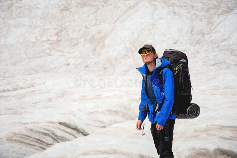 Podróżnik w nakrętce i okularach przeciwsłonecznych z plecakiem na jego brać na swoje barki w śnieżnych górach na lodowu przeciw  obrazy royalty free