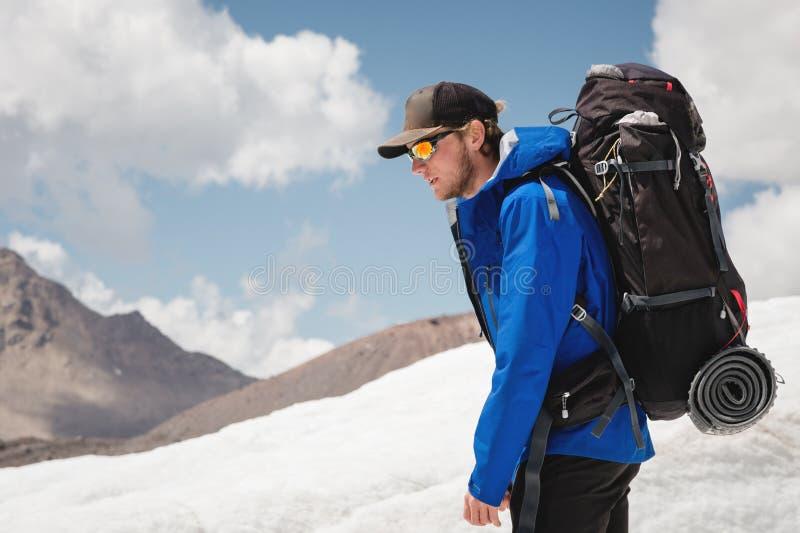 Podróżnik w nakrętce i okularach przeciwsłonecznych z plecakiem na jego brać na swoje barki w śnieżnych górach na lodowu przeciw  obraz royalty free