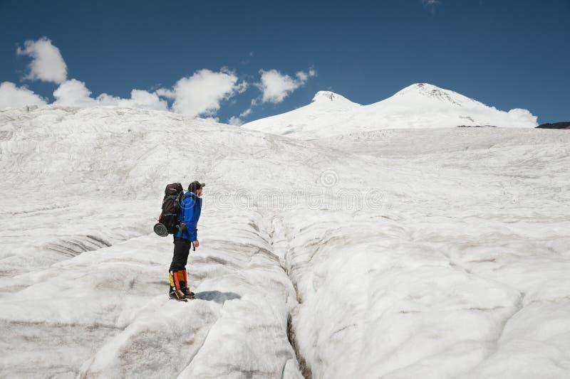 Podróżnik w nakrętce i okularach przeciwsłonecznych z plecakiem na jego brać na swoje barki w śnieżnych górach na lodowu przeciw  fotografia royalty free