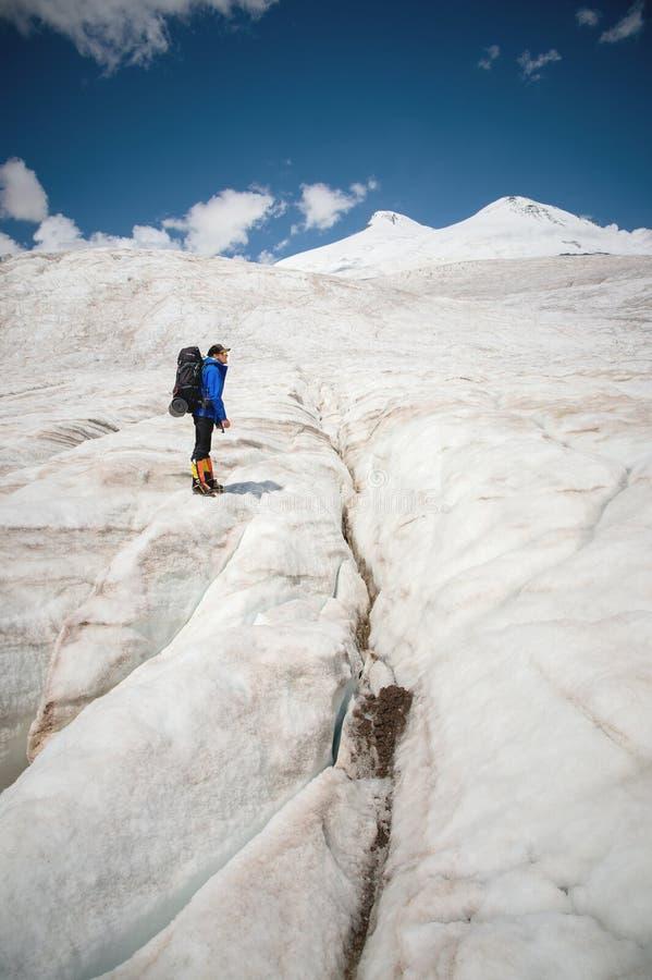 Podróżnik w nakrętce i okularach przeciwsłonecznych z plecakiem na jego brać na swoje barki w śnieżnych górach na lodowu przeciw  obraz stock