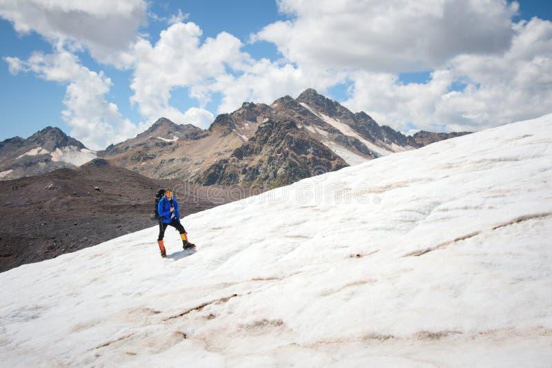 Podróżnik w nakrętce i okularach przeciwsłonecznych z plecakiem na jego brać na swoje barki w śnieżnych górach na lodowu przeciw  fotografia stock