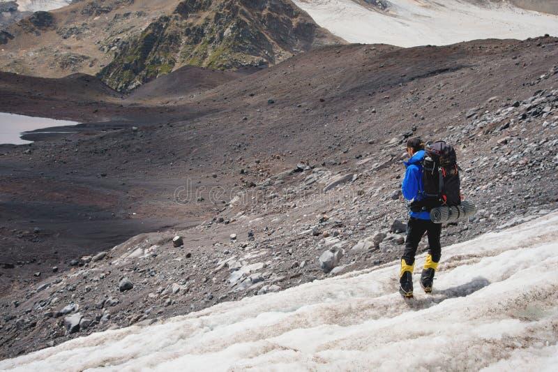 Podróżnik w nakrętce i okularach przeciwsłonecznych z plecakiem na jego brać na swoje barki w śnieżnych górach na lodowu przeciw  zdjęcia royalty free