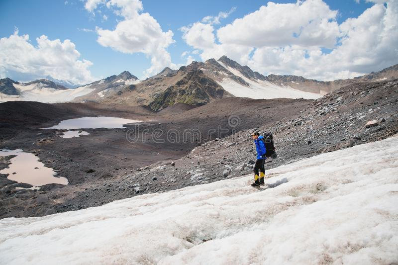 Podróżnik w nakrętce i okularach przeciwsłonecznych z plecakiem na jego brać na swoje barki w śnieżnych górach na lodowu przeciw  zdjęcia stock