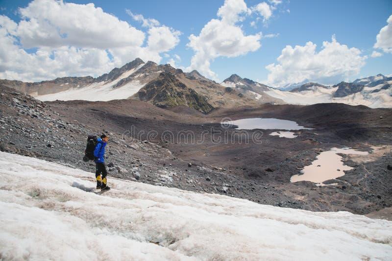 Podróżnik w nakrętce i okularach przeciwsłonecznych z plecakiem na jego brać na swoje barki w śnieżnych górach na lodowu przeciw  zdjęcie royalty free