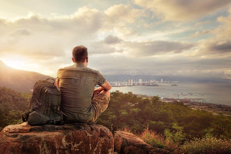 Podróżnik z plecakiem cieszy się zmierzch na szczycie góra zdjęcie royalty free
