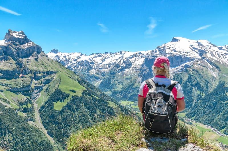 Podróżnika obsiadanie na falezie z plecakiem podziwia mountai zdjęcie royalty free