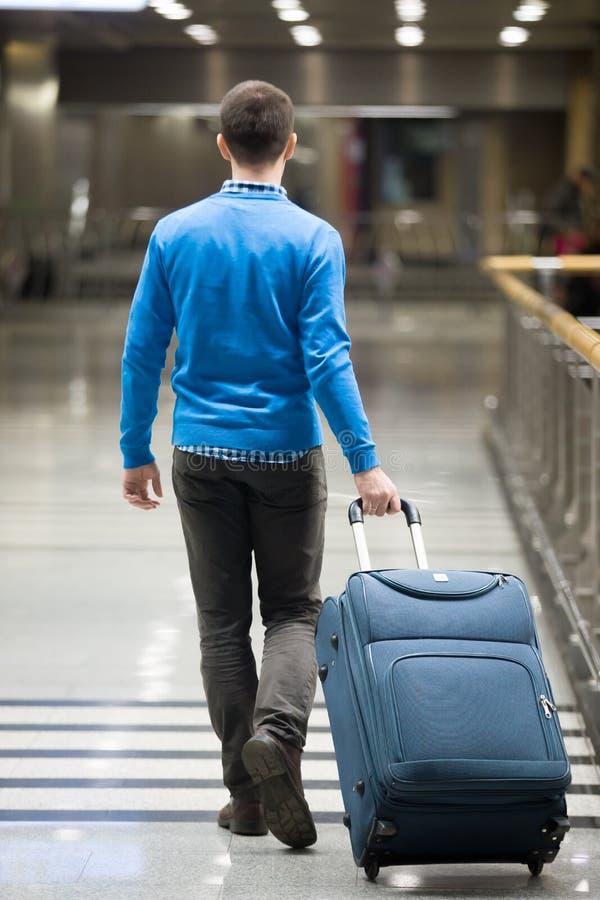 Podróżnika odprowadzenie z walizką przy lotniskiem obraz stock