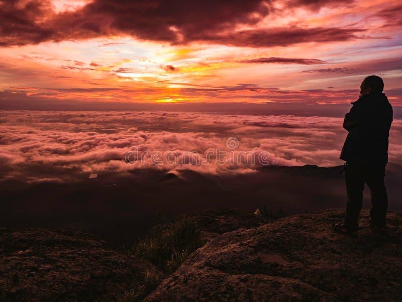 Podróżnika stojak na Skalistym cilff z sunsire niebem i piękny obłoczny morze na «Pa na raja «Khao Luang mountian obrazy royalty free